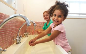 Two children wash their hands at a sink while smiling.