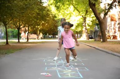 Girl plays hopscotch.