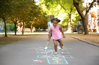 Girl plays hopscotch.