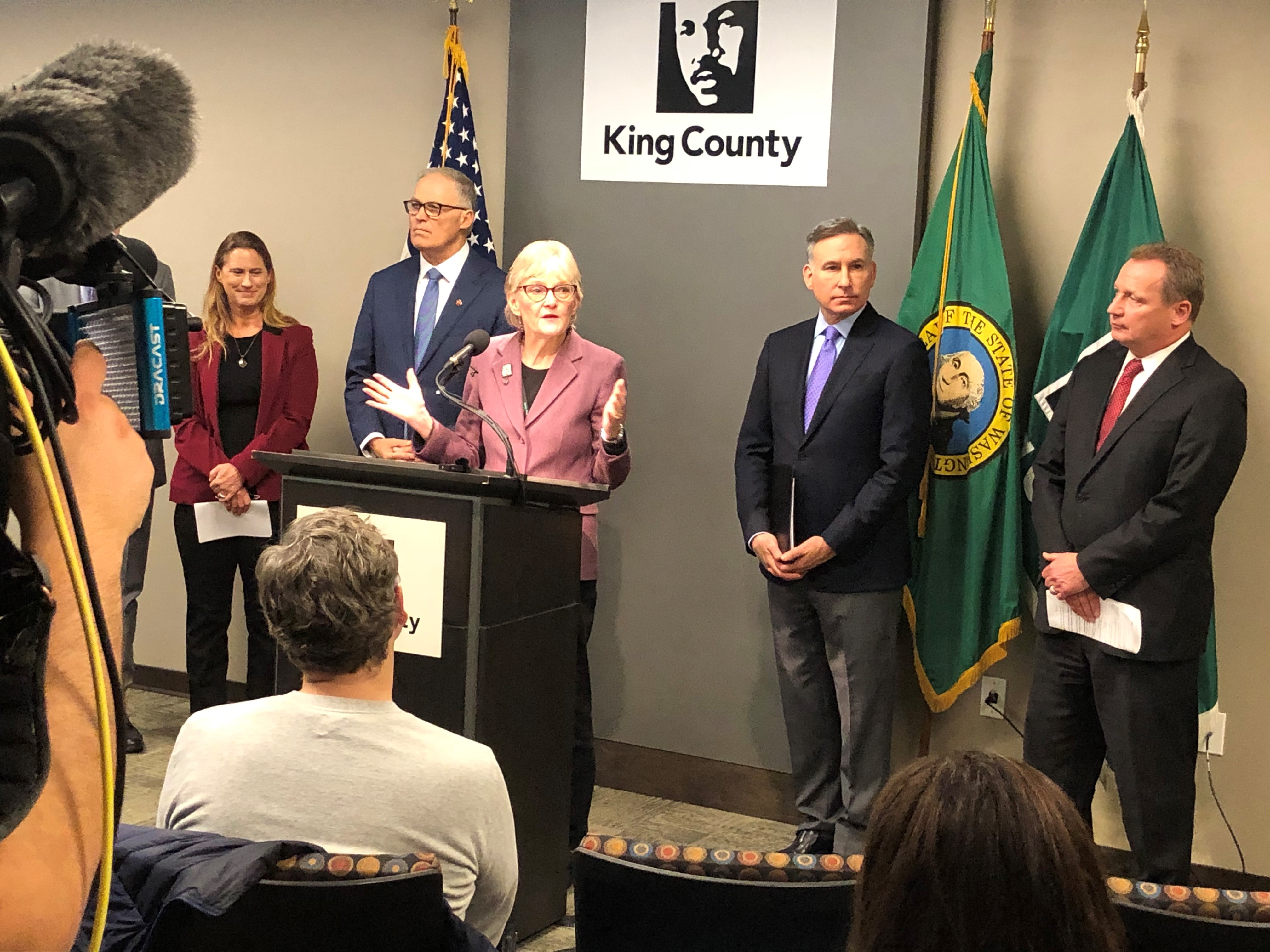 Woman at podium with King County logo behind her. People stand on either side next to flags of U.S. and WA.