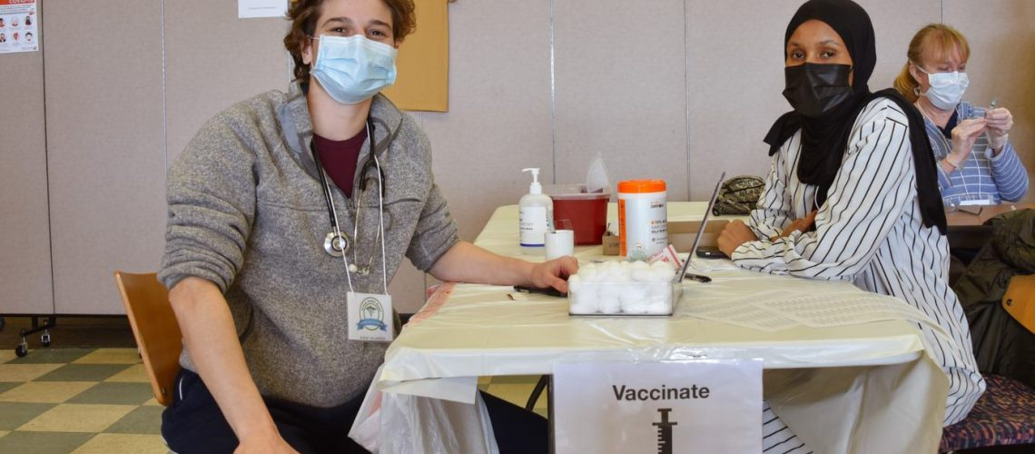 Shows a vaccinator and patient at a vaccination event