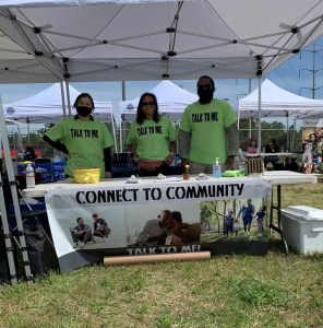 """Public health volunteers stand under tent on sunny day behind table with sign that reads """"Connect to Community"""""""