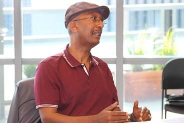 Bereket Kiros -con un gorro y una camisa roja- está hablando con el alcalde de la ciudad de Seattle, quien no está incluido en la foto