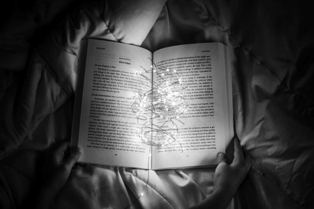 black and white image of a book held by two hands open in the middle with string lights