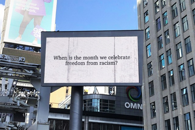 "Billboard on Yonge-Dundas square with text ""When is the month we celebrate freedom from racism?"""