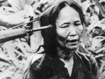 A Vietnamese civilian with a gun pointed at the side of her head. (Photo by Keystone/Getty Images)