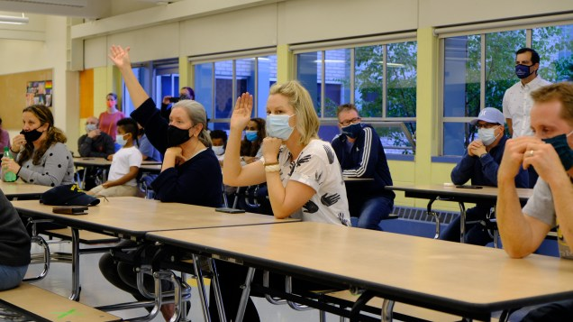Encampment neighbors raise their hands at a recent public meeting at Broadview-Thomson K-8 school.