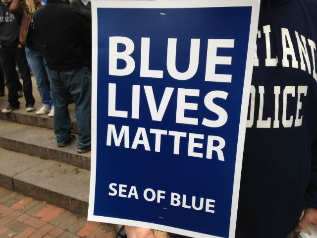 """Blue lives matter"" placard and person wearing Cleveland Police jacket at ""Sea of Blue"" rally in Cleveland, Ohio, Dec. 27. 2014 © WOIO 