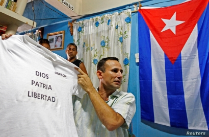 Jose Daniel Ferrer, who leads the Patriotic Union of Cuba (UNPACU), the country's largest dissident group, holds up a t-shirt…