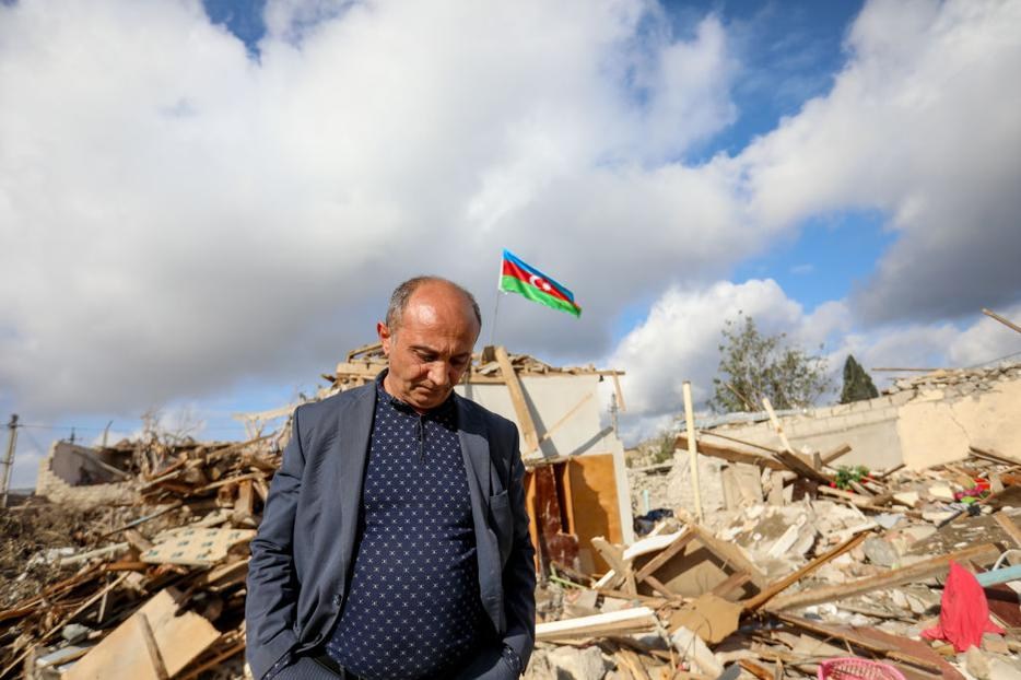 People walk by houses destroyed in a shelling attack on October 21, 2020 in Ganja, Azerbaijan.
