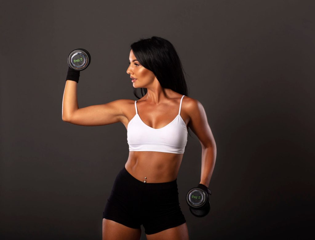 Attractive sexy fitness girl with weights on her hands