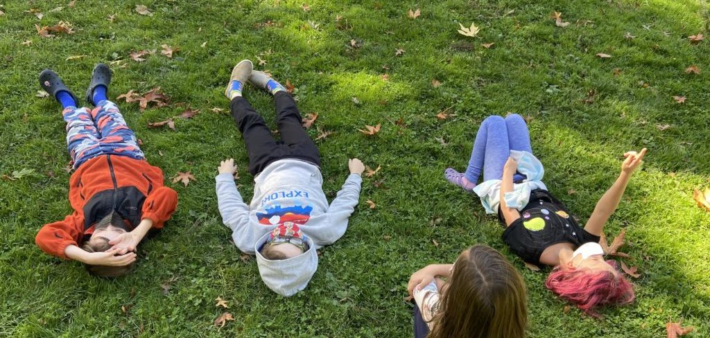 Several 4th graders lie on their backs on grass and point up to the clouds