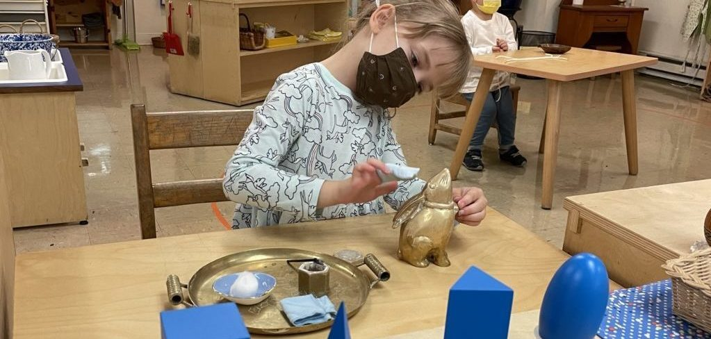A child in a classroom polishes a brass animal at a small wooden table
