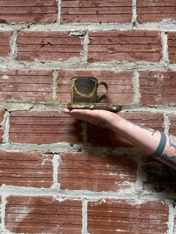 Tattooed arm holding mug and ashtray set against brick wall