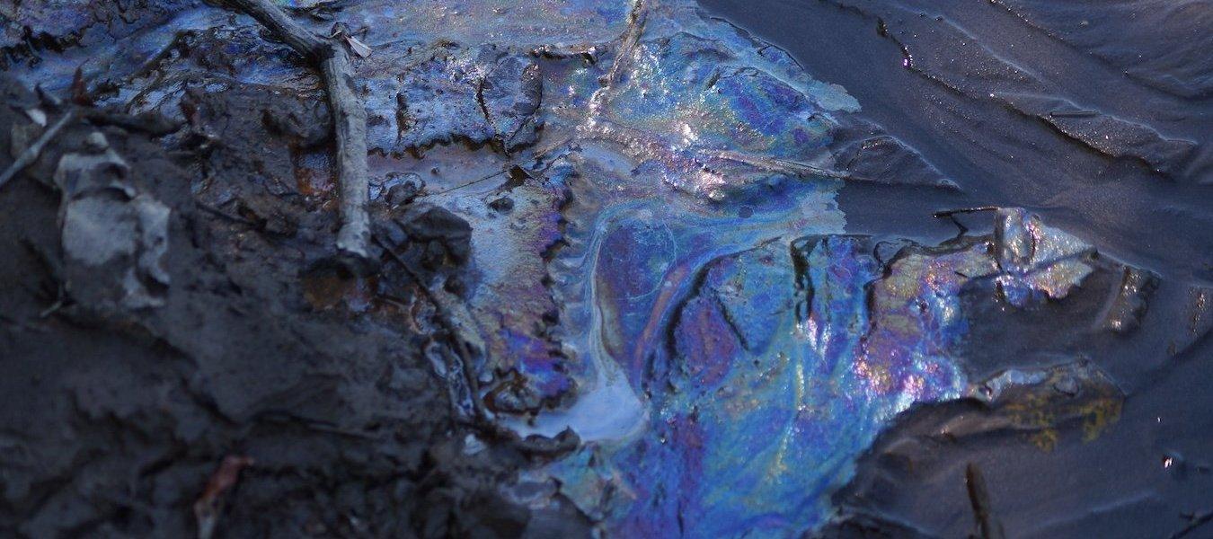 An oil sheen on a sandy surface.