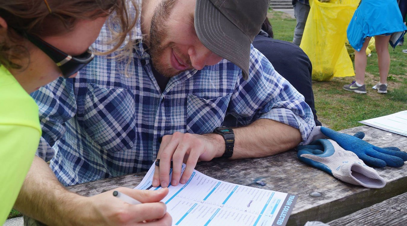 A cleanup volunteer fills out a data card at Alki Beach