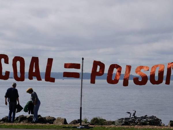 "A banner reading ""Coal = Poison"" is displayed against the Bellingham waterfront."