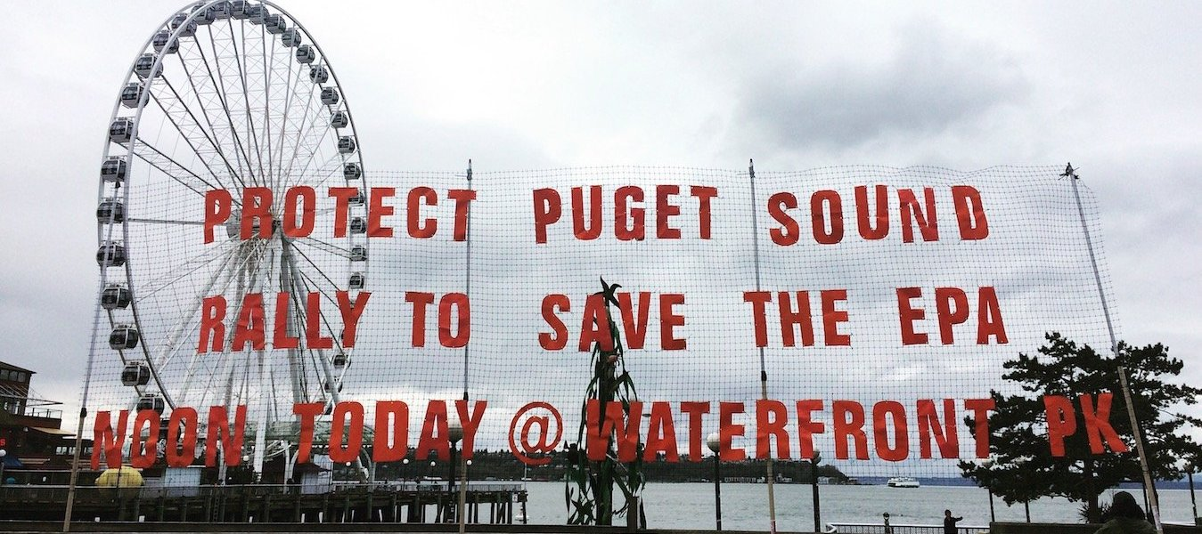 """A sign reads """"Protect Puget Sound, Rally to Save the EPA"""" in front of the Seattle Waterfront and Great Wheel."""