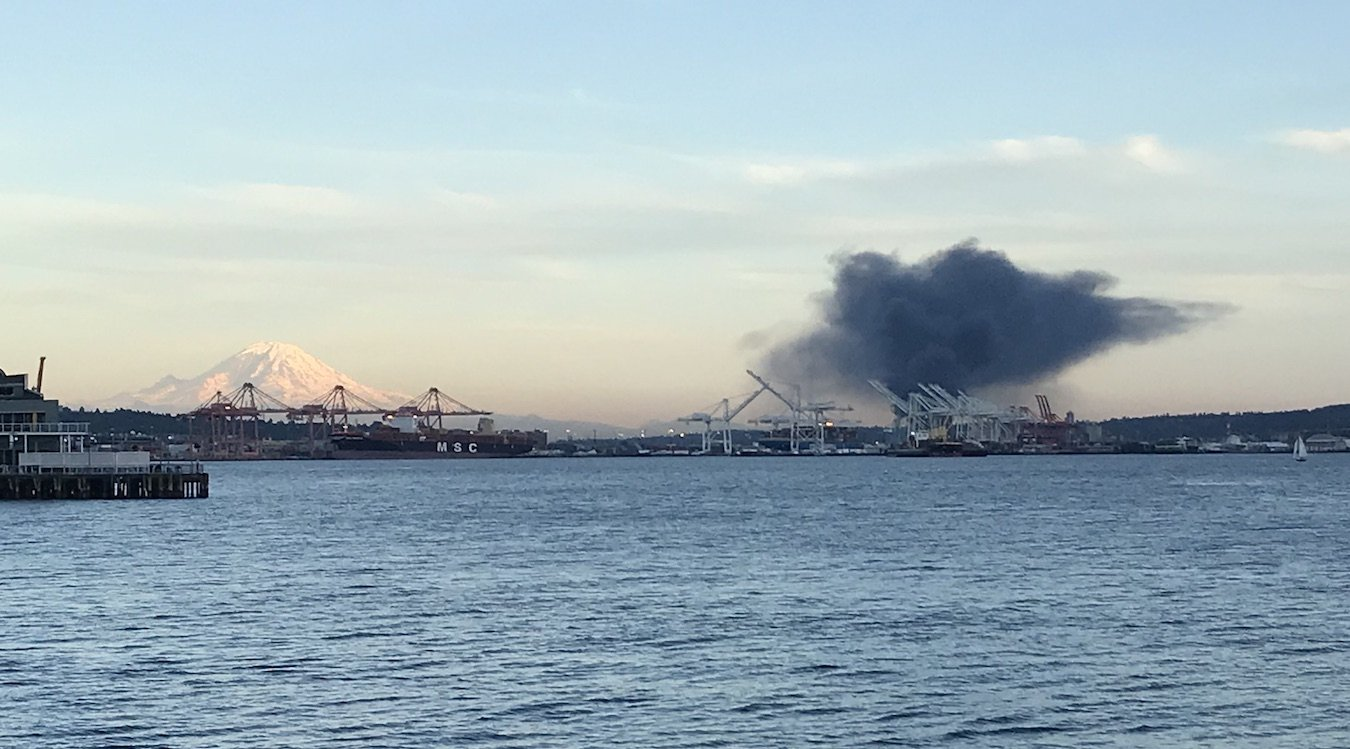A photo taken from the north end of Elliott Bay shows a black cloud of smoke rising to the right of Mount Rainier.