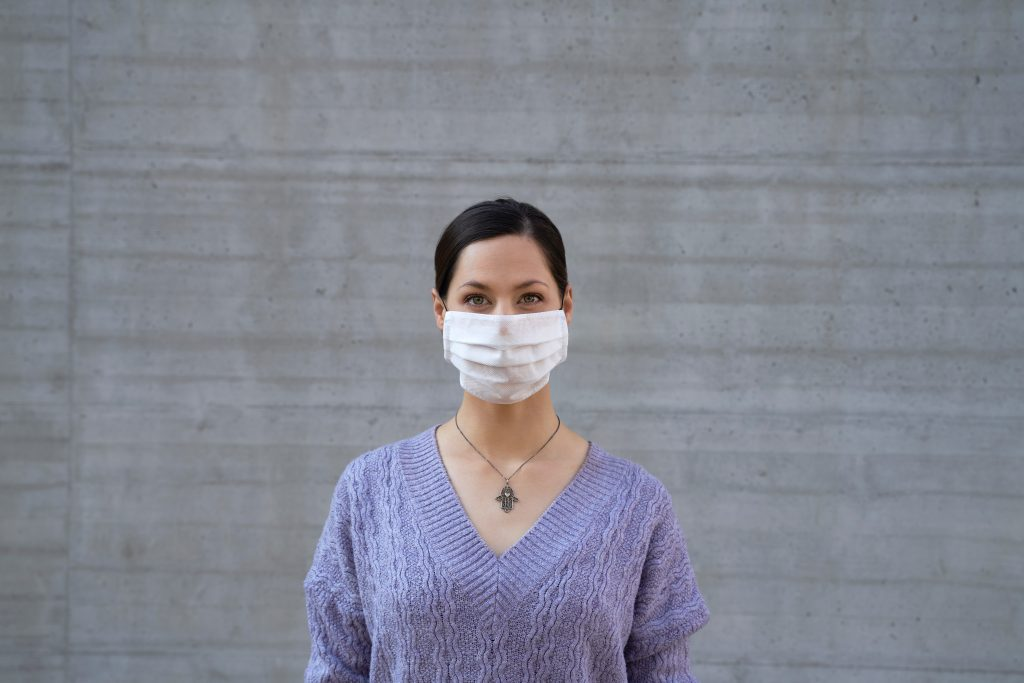Woman wears a mask and purple sweater. Grey wall as background