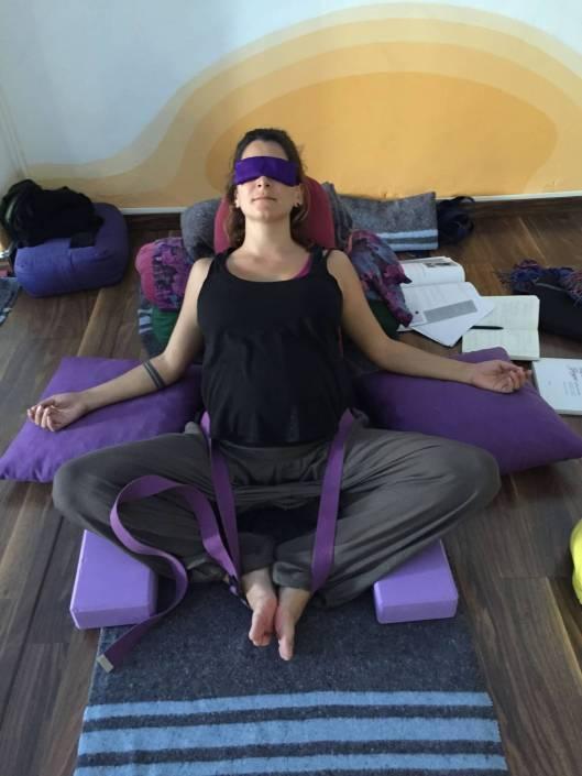 alumna de una clase de yoga restaurativo reclinada sobre una manta, bolsters, cojines y con otros accesorios en la postura del zapatero inclinada