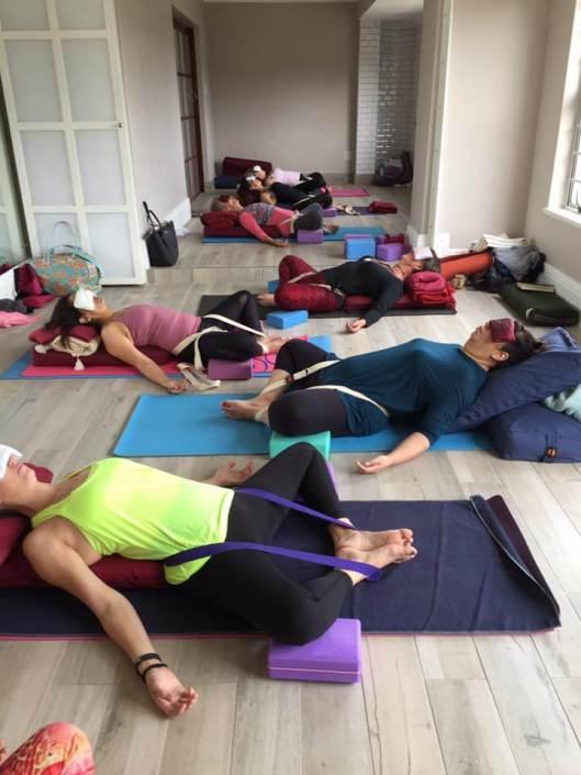 Varias alumnas de un curso en una sala de yoga con los ojos tapados por bolsas de lavanda y con posturas de relajación usando los diferentes accesorios de cojines, correas, bloques y esterillas