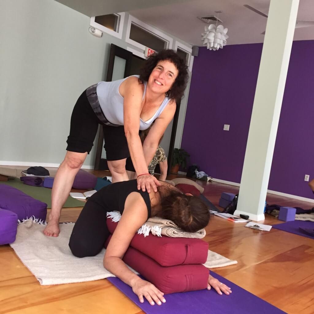 Alumna en el suelo boca abajo apoyada en dos bolsters y la profesora con sus manos apoyadas en su espalda haciendo presión para indicar la postura correcta