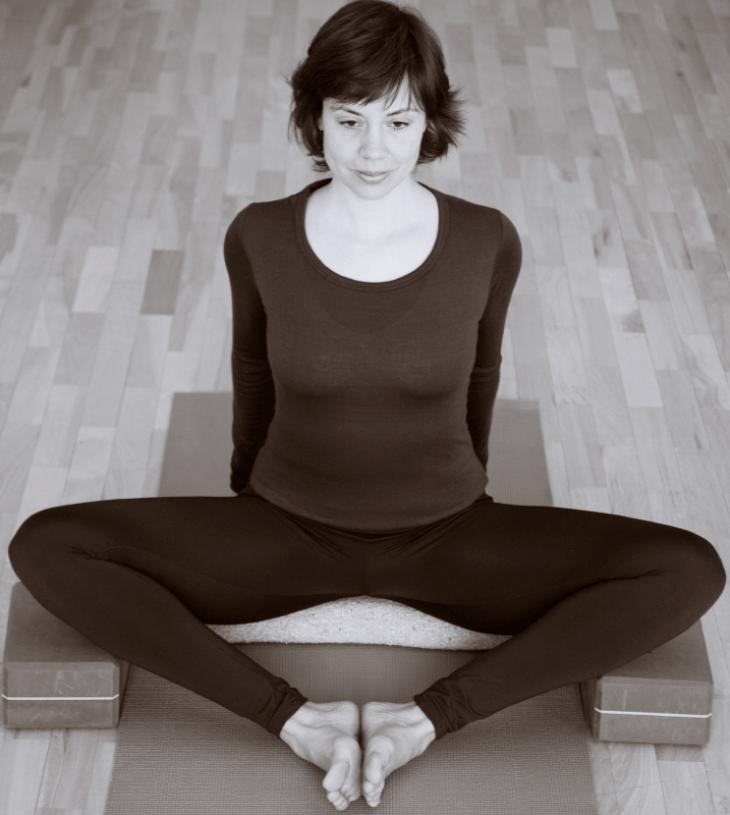 Alumna de clase de yoga sentada en una esterilla con apoyos de dos bloques y una manta en blanco y negro