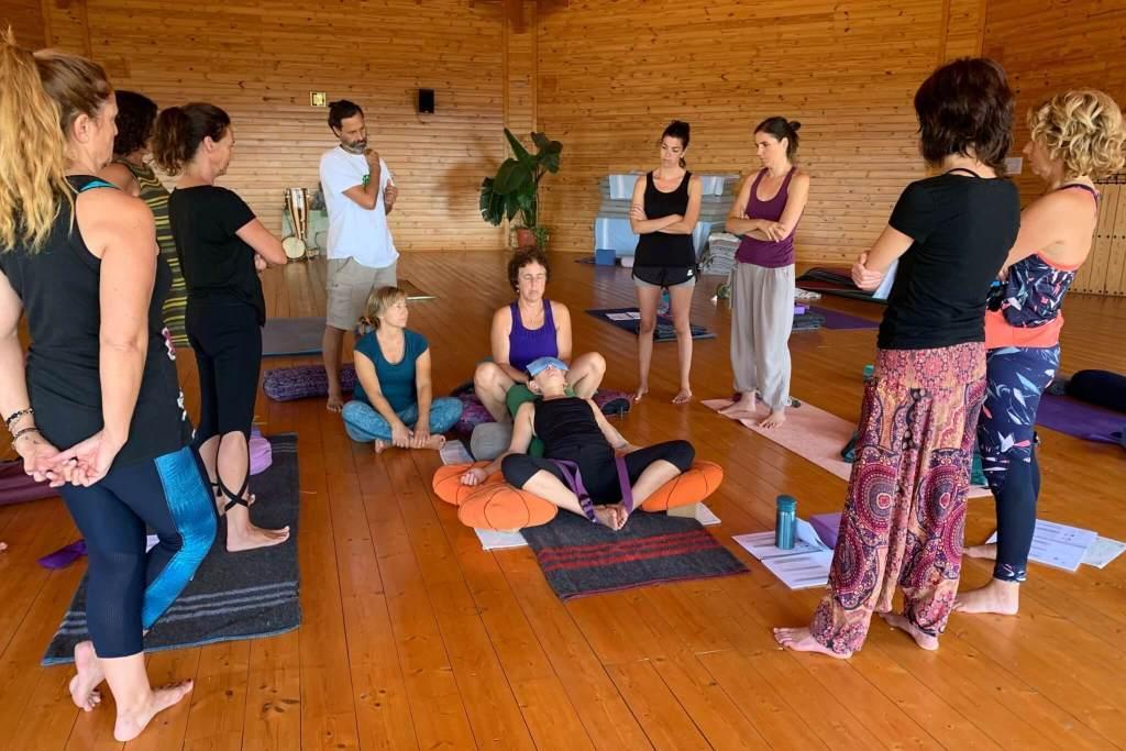 Alumnos de una formación de yoga restaurativo dispuestos en círculo observan las explicaciones de la profesora que se encuentra en el suelo con otra alumna