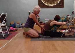 Profesora corrigiendo la postura de yoga de una alumna sentada en el suelo sobre una manta y apoyada en un cojín y una silla