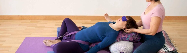 Sala de yoga donde la profesora ayuda con la postura derelajación de la alumna que está reclinada boca arriba sobre cojines, bolsters y bloques, con los ojos tapados por una bolsita de lavanda y con una correa que le sujeta los pies desde la cadera