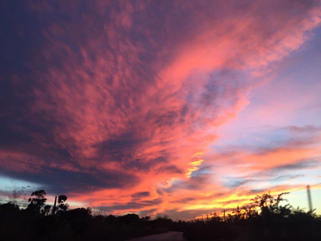 Paisaje del anochecer en el campo en un día nublado con las nubes reflejando el color rojizo del sol