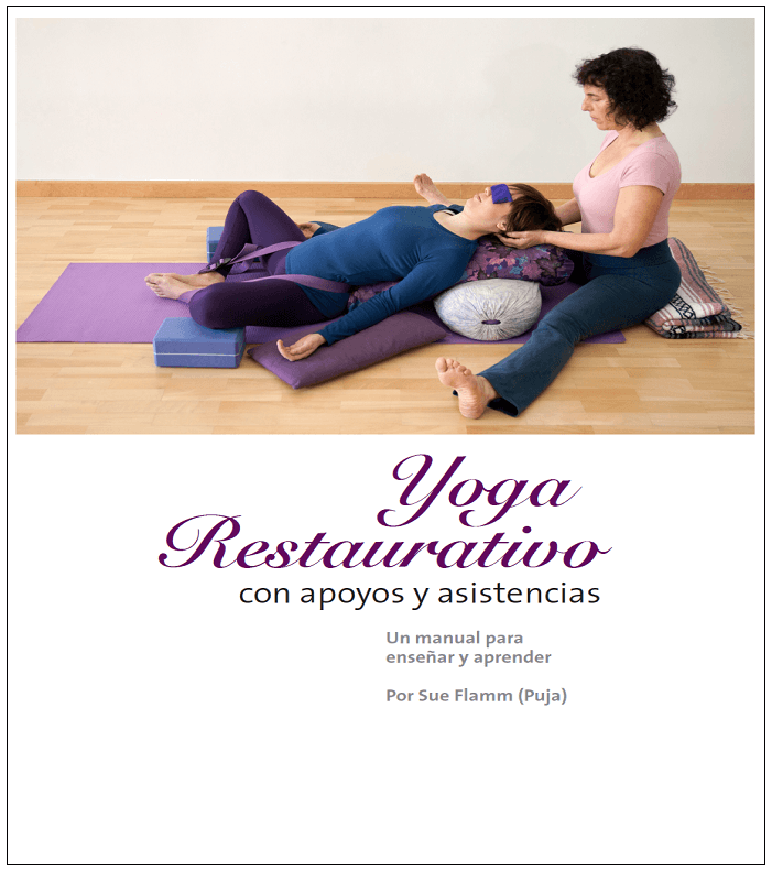 Portada en color con recuadro de línea negra del libro Yoga Restaurativo con apoyos y asistencias en español con imagen de Sue Flamm asistiendo a una alumna en una postura de yoga tumbada boca arriba y apoyada sobre bloques, cojunes y bolsters