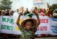 Un petit Peul manifeste devant une pancarte arrêtons le génocide lors d'une manifestation à Bamako, le 30 juin 2018. Photo MICHELE CATTANI. AFP.