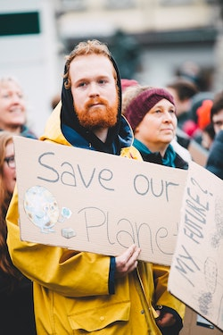 "Man holding ""save our planet"" sign"