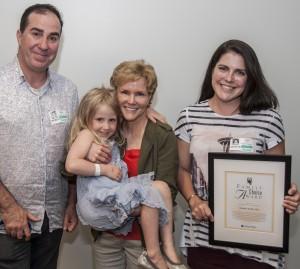 Dr. Kendra Smith (center) holds a former patient, Julia LaBelle, daughter of Colleen LaBelle (right), outgoing chair of the Family Advisory Council. At left is Julia's dad, Josh LaBelle.