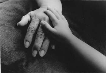 A child's hand touching an adult's hand.