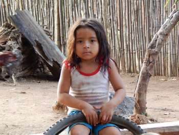 Photo of a young girl with hair to her shoulders wearing a white t-shirt and holding a bicycle tire. A wooden fence in the background.