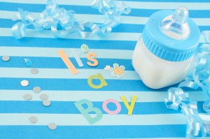 """It's a  boy"" sign and baby bottle on blue background"