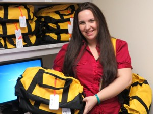 Kristina Spencer with duffels she has filled for acutely abused children discharged to foster homes.