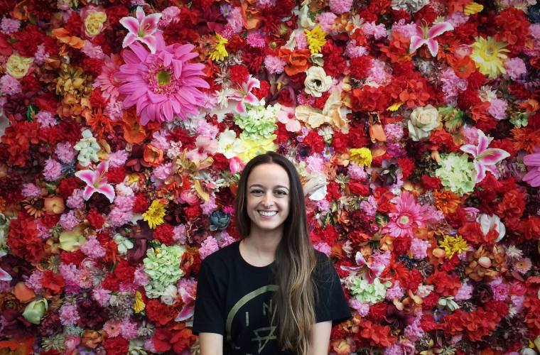 Woman standing in front of wall of flowers in Orlando, Florida