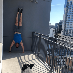 Man doing a handstand with a dog on a balcony in downtown Orlando, Florida.