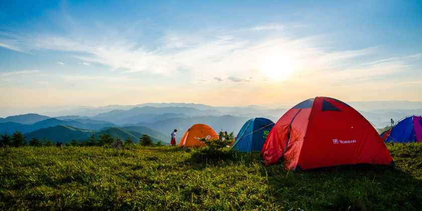 photo of pitched dome tents overlooking mountain ranges