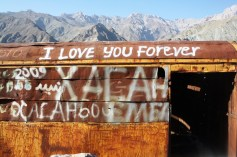 An abandoned wagon in a Tajikistan's gorge with English text on it