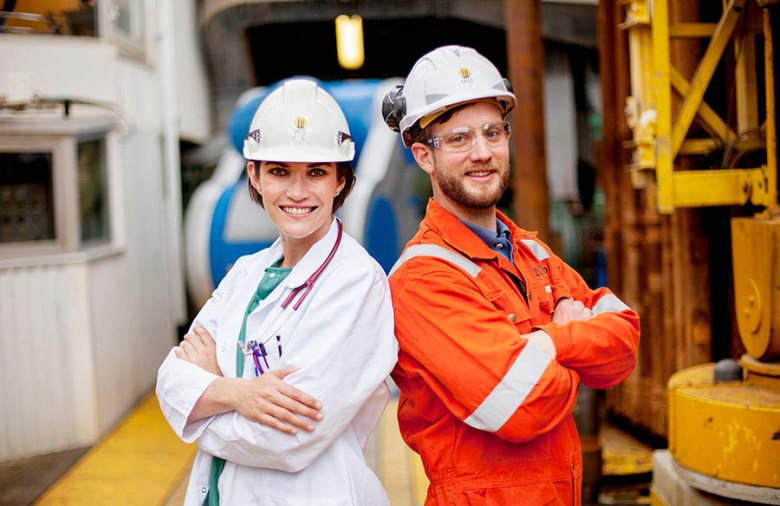 female physician wearing a white lab coat stands back to back with a male oil rig worker in orange coveralls