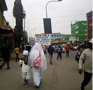 Image result for 28-year-old woman begs for husband with placard on the street
