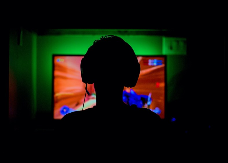 gaming addiction - silhouette of a young teenager playing a video game