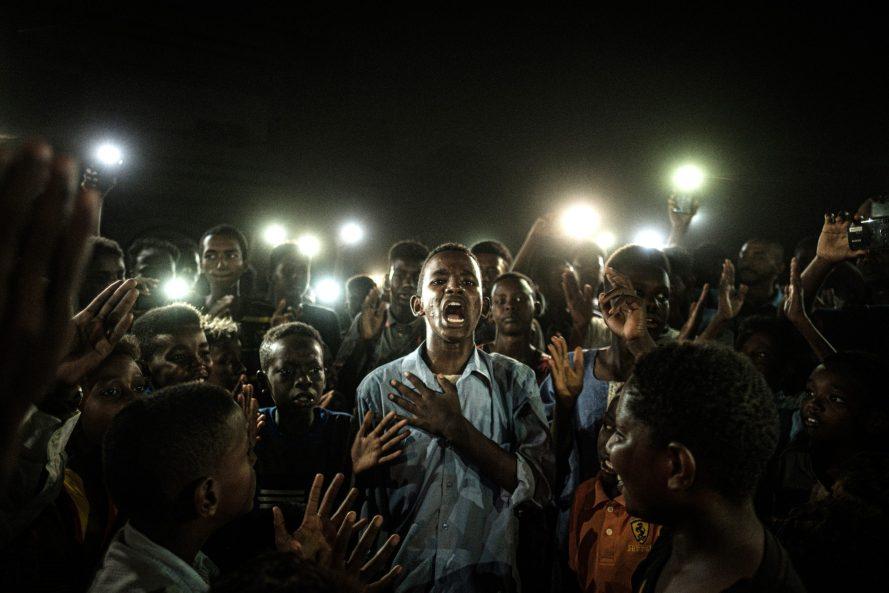 Egy szudáni fiatalember a mobiltelefonok fényében tiltakozó verset szaval, a többi tüntető polgári kormányzást követelő szlogeneket kántál a sötétben, áramszünet idején Kartúmban június 19-én. Yasuyoshi Chiba (AFP) Hír, 1. díj, egyedi