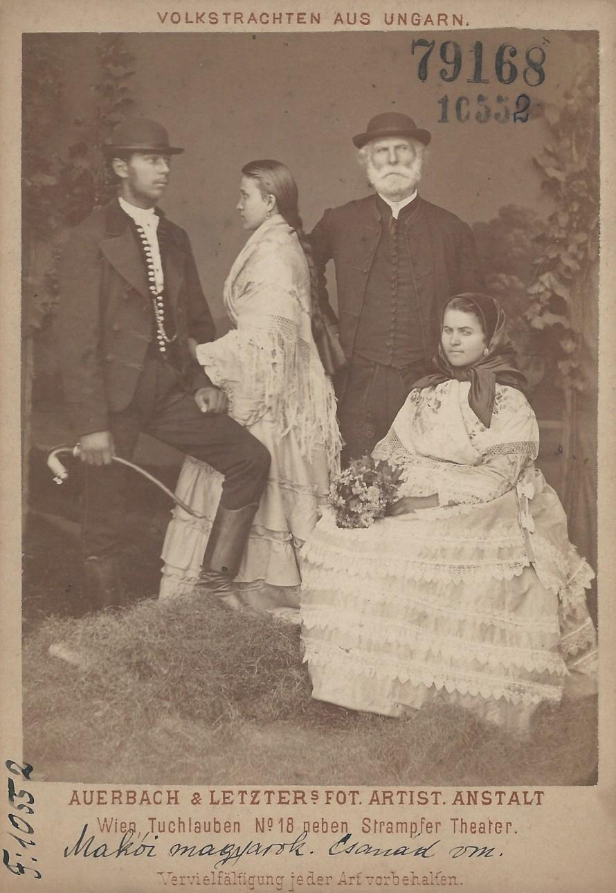 """Magyar család (?) Makóról. A lányon, fejkendős fiatalasszonyon a mezővárosi öltözet polgárosodását mutató krinolinos jellegű szoknya. A zsánerkép a """"Volkstrachten aus Ungarn"""" sorozat része, melyet Auerbach Miksa és Letzter Lázár készített az 1873-as bécsi világkiállításra. Kettejük közös vállalkozásaként Bécsben műtermet tartottak fenn, ahol feltehetően a sorozat darabjait is árusították Makó, 1872<br> Auerbach Miksa és Letzter Lázár felvétele Néprajzi Múzeum, F 10552"""