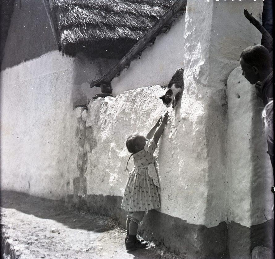 Fotó: Kislány, a kép szélén bámészkodók, Csömör, 1936<br> Vadas Ernő felvétele<br> Néprajzi Múzeum, F 268270